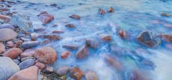 Kustdiekiezelstenen door een vloed worden behandeld stock afbeeldingen