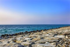 Kusten av havet med stora stenar - stenblock - vågbrytare, ljusa vågor Arkivfoton