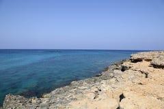 Kusten med dess steniga strand och frikändvatten Royaltyfria Bilder
