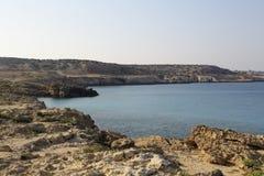 Kusten med dess steniga strand och frikändvatten Arkivbild