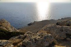 Kusten med dess steniga strand och frikändvatten Höghusskytte Arkivfoto