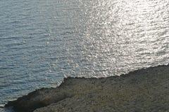 Kusten med dess steniga strand och frikändvatten Höghusskytte Arkivbilder
