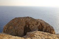 Kusten med dess steniga strand och frikändvatten Höghusskytte Royaltyfri Fotografi