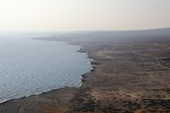 Kusten med dess steniga strand och frikändvatten Höghusskytte Royaltyfri Bild