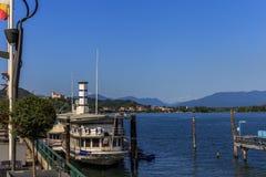 Kuster av sjön Maggiore med växter, solen och fartyg Royaltyfri Bild