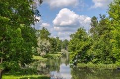 Kusterna av sjön som omges av den gröna skogen och ängen i parkera av Gatchina royaltyfri fotografi
