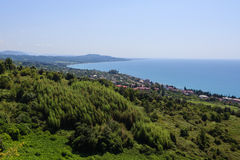 Kustlandschap met groen bos en huizen in Nieuwe Athos royalty-vrije stock afbeeldingen