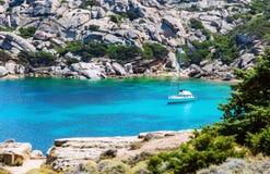Kustlijn met eenzaam jacht in Sardinige stock afbeelding