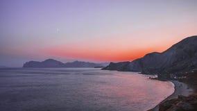 Kustlijn met gradiënthemel en rotsen na zonsondergang Royalty-vrije Stock Fotografie