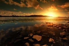 Kustlijn met stenen en zonsondergang Royalty-vrije Stock Afbeelding