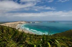 Kustlijnmening van Kaap Reinga met blauwe hierboven hemel en witte wolken, Northland, Nieuw Zeeland stock fotografie
