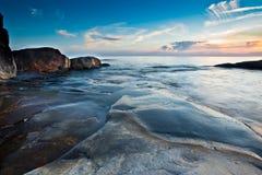 kustlinje över stenig solnedgång Arkivbilder
