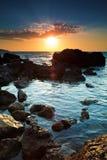 kustlinje över stenig solnedgång Arkivfoto