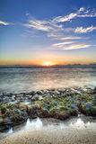 kustlinje över stenig solnedgång Arkivfoton