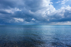 Kustlinje för blått vatten på molnig dag Arkivbild