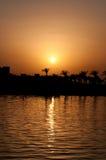 Kustlinje mot med bakgrund av havssolnedgången Arkivbild
