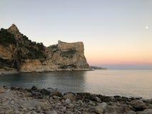 Kustlinje och dramatisk klippa på solnedgången med månestigningen arkivfoton