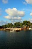 Kustlinje, pir och turister som strosar längs stranden Arkivbild