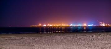 Kustlinjen av den Blankenberge stranden som tänds vid natten, färgrika ljus på branschterrängen i avståndet royaltyfri foto