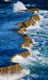 Kustlinjen på halvön Valdes mot krascha rockswaves arenaceous Royaltyfri Fotografi