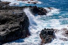 Kustlinjevågor som bryter över vulkaniskt, vaggar arkivfoto