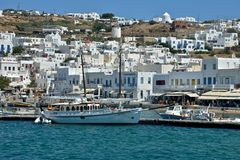 Kustmening van Mykonos met witte gebouwen en haven met varend vastgelegd schip stock afbeelding