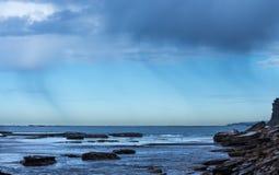 Kustregen die over de oceaan tegen blauwe hemel met de richel van de kustrots vallen stock foto's