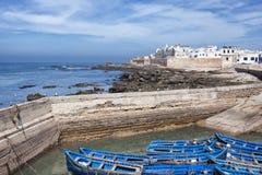 Kuststad met overzees en blauwe boten. Stock Fotografie
