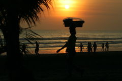 Kuta Bali Beach. Locals on Kuta beach Bali, Local Lady crries basket on her head going home after selling fruit to Tourests royalty free stock photo