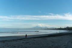 Kuta BALI 13 DE MARÇO DE 2019: Povos na praia do mar tropical com barco, a onda, a montanha e as nuvens tradicionais no fundo fotografia de stock