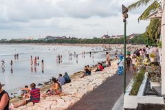 Locals and tourists gather at the foreshore to enjoy and photograph the Balinese sunset. Kuta, Bali / Indonesia - 11/20/2016 Locals and tourists gather at the royalty free stock photography
