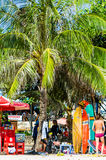 Kuta Beach, Bali, Indonesia, Southeast Asia. KUTA,INDONESIA- JULY 24 : People sit on Kuta beach, Bali under a coconut palm next to some surf boards on the 24th royalty free stock images