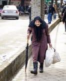 KUTAISI, GEORGIA - 23. FEBRUAR 2016: ältere Frau, die auf die Brücke über dem Fluss Rioni geht Stockfotografie