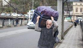 KUTAISI, GEORGIA - 23. FEBRUAR 2016: der Mann trägt Waren gehend auf die Brücke über dem Fluss Rioni Stockfotografie
