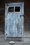 KUTAISI - GEORGIA - JULY 2016: Blue-grey wooden vintage door. Old door with rusty lock. Near door standing a dirty ceramic plate. Concept: dilapidated, old time Stock Photos