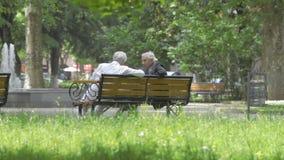Kutaisi, Georgia - mayo de 2017: Dos viejos hombres georgianos que hablan sentarse en banco de parque Kutaisi, Georgia almacen de video