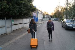 KUTAISI, GEORGIA - 11 11 2018: Two teenagers travel with their luggage, one with a suitcase and the other with a backpack stock images