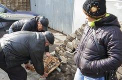 KUTAISI, LA GÉORGIE - 23 FÉVRIER 2016 : des hommes plus âgés vendent la viande sur le marché en plein air Photos stock