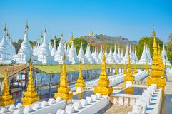The beautiful cityscape of Mandalay, Myanmar. The Kuthodaw Pagoda is one of the most unusual places in Mandalay with numerous white stupas located on the stock photo