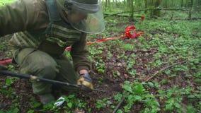 KUTINA KROATIEN - JUNI 2014: Man som försöker att avkänna minen i minröjningprocess i mitt av skogen stock video