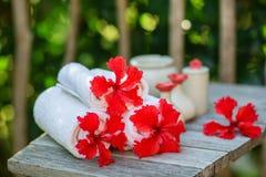 Kuuroord die met handdoeken en rode hibiscusbloemen plaatsen Stock Foto