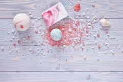 Kuuroord en douchetoebehoren Badbommen, aromatherapy zoute, met de hand gemaakte zeepbar en zeeschelpen op houten achtergrond Stock Foto's