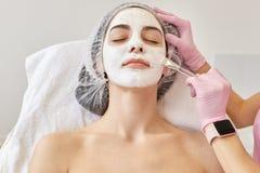 Kuuroord en huidzorgconcept Jonge vrouw met gezichtsmasker in schoonheidssalon, cosmetologist die speciale borstel voor het appla royalty-vrije stock afbeeldingen