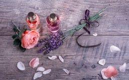 Kuuroord met roze bloemblaadjesolie, Geparfumeerde Rose Water in glasflessen en lavendel met purper lint op houten achtergrond wo royalty-vrije stock fotografie