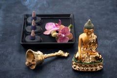 Kuuroord met standbeeld Boedha, zen zwarte stenen, orchidee en wierook Stock Afbeeldingen