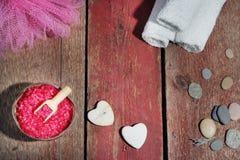 Kuuroord op een houten rode achtergrond, een badzout, een luffa, witte handdoeken en stenen in de vorm van harten wordt geplaatst Stock Foto's