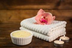 Kuuroord of wellnessreeks Geel overzees zout in witte kom, handdoeken, cand Royalty-vrije Stock Foto's