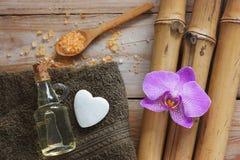Kuuroordachtergrond met bamboe, badzout, massageolie, orchideebloem, handdoek en steen in de vorm van hart stock foto's