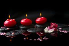 Kuuroordconcept witte en rode orchidee (cambria), drie rode kaarsen Stock Foto's