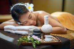 Kuuroordconcept, Zen-stenen, Kaarsen en bloemen op de achtergrond die van vrouw behandeling, Jonge mooie vrouw in kuuroord ontvan royalty-vrije stock foto's